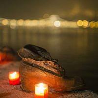 Des bougies brûlent devant les chaussures en fonte du Mémorial de la Shoah sur le quai du Danube, pendant la Journée internationale de commémoration de la Shoah à Budapest, Hongrie, le mercredi 27 janvier 2016. (Balazs Mohai/MTI via AP)
