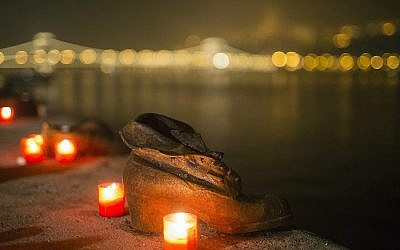 Des bougies brûlent devant les chaussures en fonte du Mémorial de la Shoah sur le quai du Danube, pendant la Journée internationale de commémoration de la Shoah à Budapest, Hongrie, le mercredi 27 janvier 2016 (Balazs Mohai/MTI via AP)
