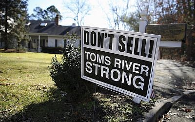 """Une pancarte disant : """"Don't Sell! Toms River Strong"""" [""""Ne vendez pas! Toms River résiste""""], dans une rue de Toms River (New Jerseay), le lundi 22 février 2016. Une crise du logement dans la ville côtière du New Jersey qui abrite l'une des plus grandes populations hassidiques du pays a poussé les villes voisines à changer leurs propres lois. Des agents immobiliers et des investisseurs de la région de Lakewood ont sollicité des résidents de plusieurs quartiers avoisinants afin de trouver des maisons qui répondent aux besoins de la communauté juive croissante. (AP Photo/Mel Evans)"""