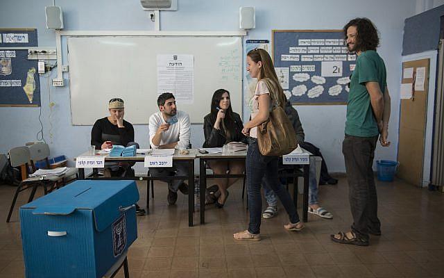 Des Israéliens se préparent à voter dans un bureau de vote à Tel Aviv, pour le 20e Parlement, lors des élections générales israéliennes, le 17 mars 2015. (Danielle Shitrit/FLASH90)