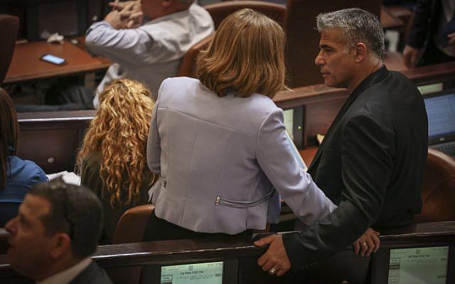 Les députés Tzipi Livni, (à gauche), et Yair Lapid, à droite, discutent à la Knesset le 13 mai 2015 (Crédit :  Hadas Parush/Flash90)