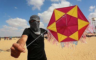 Un manifestant palestinien montre un cerf-volant chargé d'un engin incendiaire avant de le lancer vers Israël, à l'est de Rafah dans le sud de la bande de Gaza, le 29 juin 2018. (Abed Rahim Khatib/Flash90)