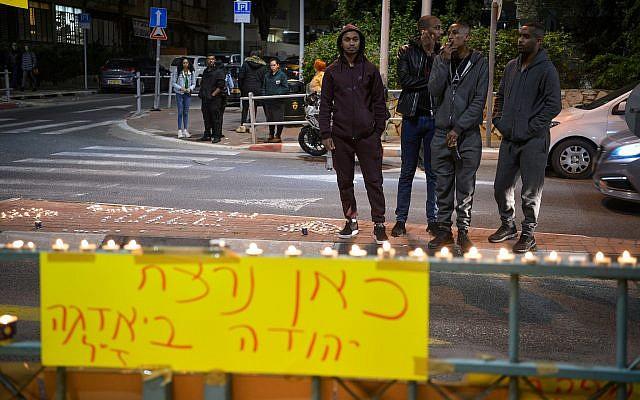 """Des bougies allumées sur le site où l'Israélien d'origine éthiopienne Yehuda Biadga a été tué alors qu'il se ruait vers un policier, un couteau à la main, à Bat Yam, le 20 janvier 2019. Une bannière dit : """"Yehuda Biadga a été assassiné ici"""" (Crédit : Flash90)"""