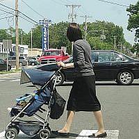 Une femme orthodoxe pousse une poussette à Lakewood (New Jersey) en 2013. La population de la ville orthodoxe en grande partie haredi a explosé au cours des deux dernières décennies, et les familles haredi cherchent à s'installer dans les villes voisines. (Dennis Fraevich/Flickr via JTA)