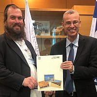 Yechiel Charaz (G) recevant un certificat lui permettant d'accueillir des visites guidées en langue yiddish des mains du ministre du Tourisme Yariv Levin à Jérusalem, le 13 janvier 2019. (Ministère du Tourisme)