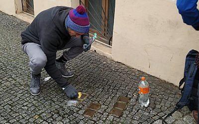 """Des bénévoles nettoient des """"stolpersteine"""" dans le quartier de Kreuzberg à Berlin lors de la Journée internationale de commémoration de la Shoah, le 27 janvier 2019. (Yaakov Schwartz/Times of Israel)"""