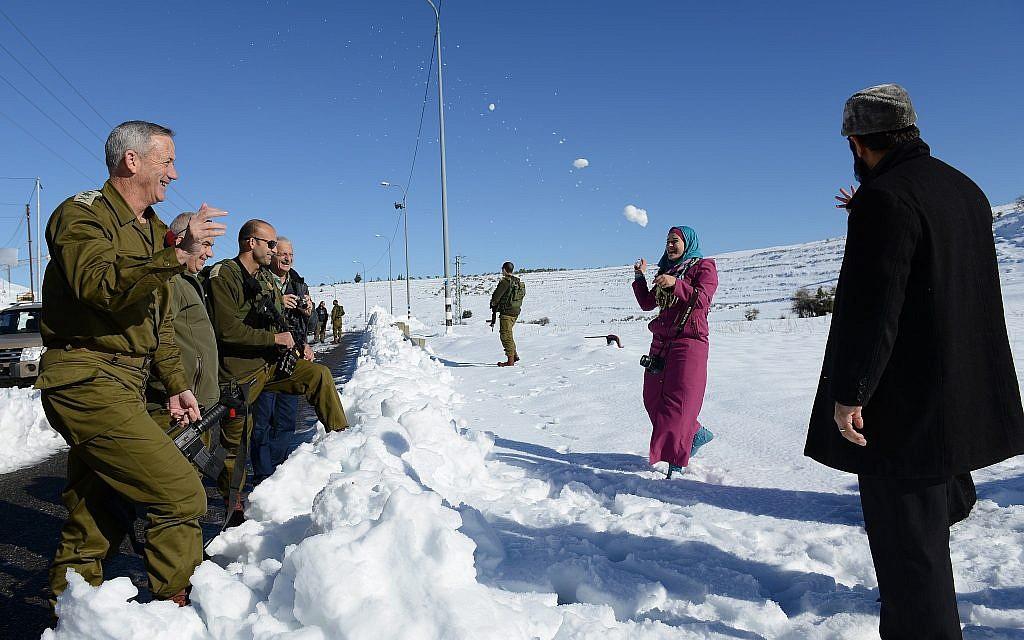 Le chef d'état-major de Tsahal de l'époque, Benny Gantz, fait une bataille de boules de neige avec une famille palestinienne le long de la route 60 en Cisjordanie, le 15 décembre 2013. (Judah Ari Gross / Armée israélienne)