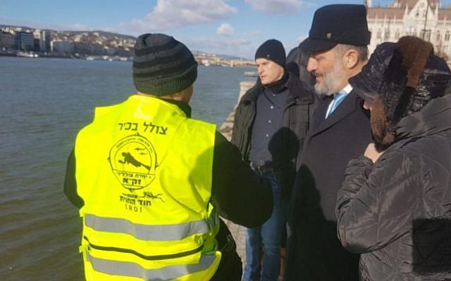 Un plongeur de ZAKA explique au ministre de l'Intérieur Aryeh Deri, la procédure de recherche des restes des victimes de la Shoah dans le Danube en Hongrie, en janvier 2019. (Avec l'aimable autorisation de ZAKA)