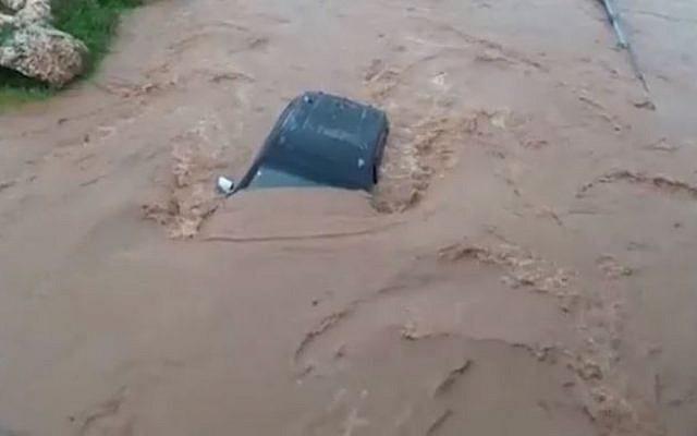 Une voiture emportée par les eaux dans le lit de la rivière de Hilazon dans le centre de la Galilée, le 14 janvier 2019 (Crédit : Services des incendies et de secours du district du nord)