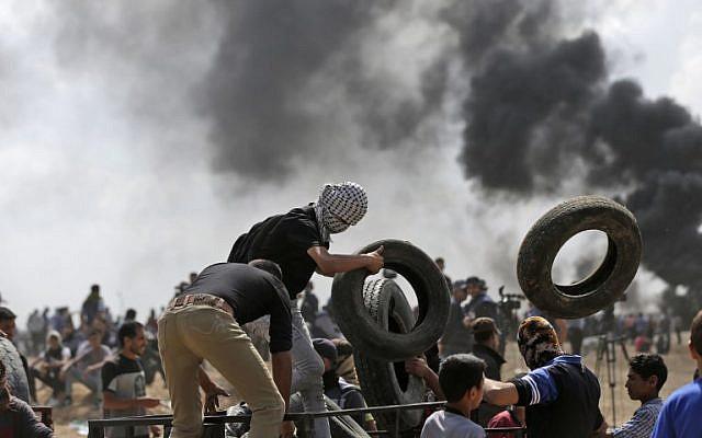 Des manifestants palestiniens brûlent des pneus près de la frontière entre Gaza et Israël, à l'est de la ville de Gaza, lors de manifestations contre l'inauguration de l'ambassade des États-Unis à Jérusalem, le 14 mai 2018. (AFP Photo/Mahmud Hams)