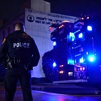 Un agent de police sous la pluie aux abords de la synagogue Tree of Life après une fusillade qui a fait onze morts dans le quartier de Squirrel Hill à  Pittsburgh le 27 octobre 2018 (Crédit : Brendan Smialowski / AFP)