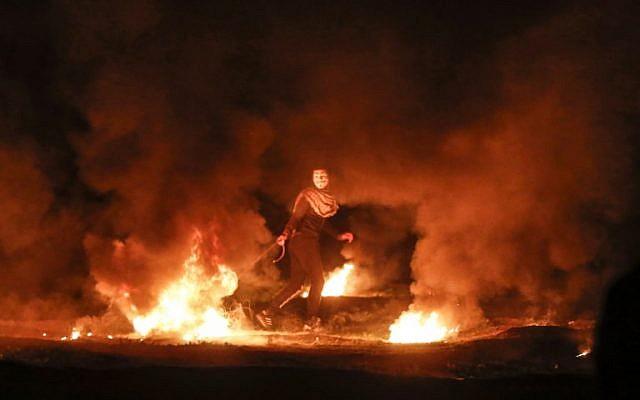 Un manifestant palestinien masqué traîne un pneu en flammes pendant une manifestation nocturne près de la clôture le long de la frontière avec Israël, à l'est de la ville de Gaza, le 11 février 2019. (Photo par MAHMUD HAMS / AFP)