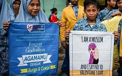 """Une centaine de lycéens de Surabaya, la deuxième ville d'Indonésie, manifestent contre la tradition occidentale de la Saint-Valentin. """"Dites non maintenant à la Saint-Valentin!"""" ou """"Désolée pour la Saint-Valentin, je suis musulmane"""", peut-on lire sur les pancartes. (Crédit : .Juni Kriswanto / AFP)"""