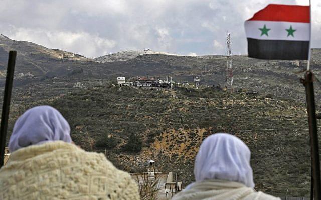 Des femmes druzes de Majdal Sham, sur le plateau du Golan, regardent de l'autre côté de la frontière, le 14 février 2019 (Crédit : JALAA MAREY / AFP)