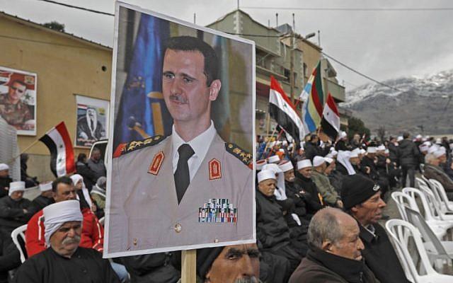 Des résidents druzes du plateau du Golan portent un portrait du président syrien Bashar al-Assad pendant un rassemblement dans le village de Majdal Shams, le 14 février 2019 (Crédit :  JALAA MAREY / AFP)