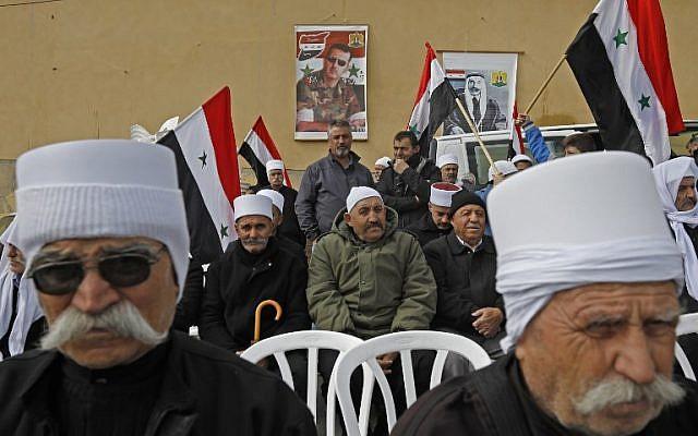 Les portraits du président Bashar al-Assad, au centre, et de feu le leader druze arabe Sultan al-Atrash, à droite, en arrière-plan pendant une manifestation à Madjal Shams, le 14 février 2019 (Crédit :JALAA MAREY / AFP)