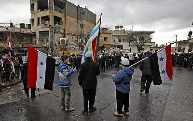 De jeunes résidents druzes sur le plateau du Golan brandissent les drapeaux syrien et druze durant un rassemblement dans le village de Majdal Shams sur le plateau du Golan, le 14 février 2019 (Crédit : JALAA MAREY / AFP)