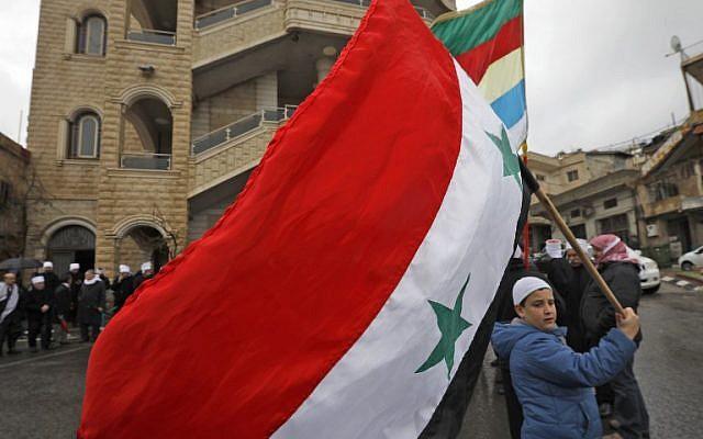 Un jeune résident druze du plateau du Golan brandit le drapeau national syrien durant un rassemblement dans le village de Majdal Shams, sur le plateau du Golan, le 14 février 2019 (Crédit :  JALAA MAREY / AFP)