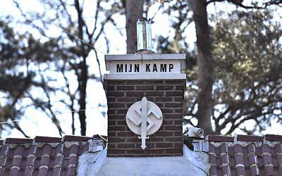 """Une photo prise à Keerbergen, dans le nord de la Belgique le 15 février 2019 montre une swastika sur laquelle on peut lire 'Mijn Kamp' (""""Mon Camp"""", en référence détournée à """"Mein Kampf"""") sur la cheminée de la maison décorée d'autres symboles nazis (Crédit : DIRK WAEM / BELGA / AFP)"""
