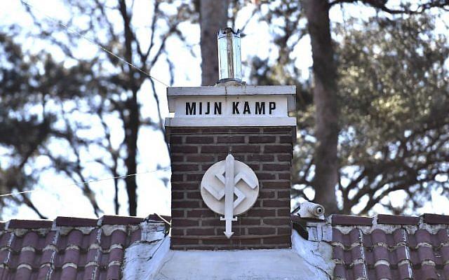 """Une photo prise à Keerbergen, dans le nord de la Belgique le 15 février 2019 montre une swastika sur laquelle on peut lire 'Mijn Kamp' (""""Mein Kampf"""" en flamand) sur la cheminée de la maison décorée d'autres symboles nazis (Crédit: DIRK WAEM / BELGA / AFP)"""