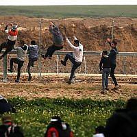 Des Palestiniens escaladent la clôture de sécurité le long de la frontière entre Israël et la bande de Gaza, lors d'affrontements à l'est de la ville de Gaza, le 15 février 2019. (Saïd Khatib/AFP)