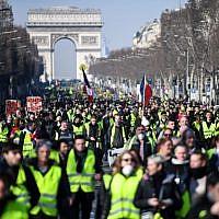 """Des manifestants défilent sur l'avenue des Champs-Élysées le 16 février 2019, lors de la 14e semaine consécutive de manifestations des """"Gilets jaunes"""". (Crédit : Eric Feferberg/AFP)"""