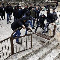 Des manifestants palestiniens défoncent des portes verrouillées dans l'enceinte de la mosquée Al Aqsa sur le Mont du Temple, dans la Vieille Ville de Jérusalem, le 18 février 2019. (Ahmad Gharabli/AFP)