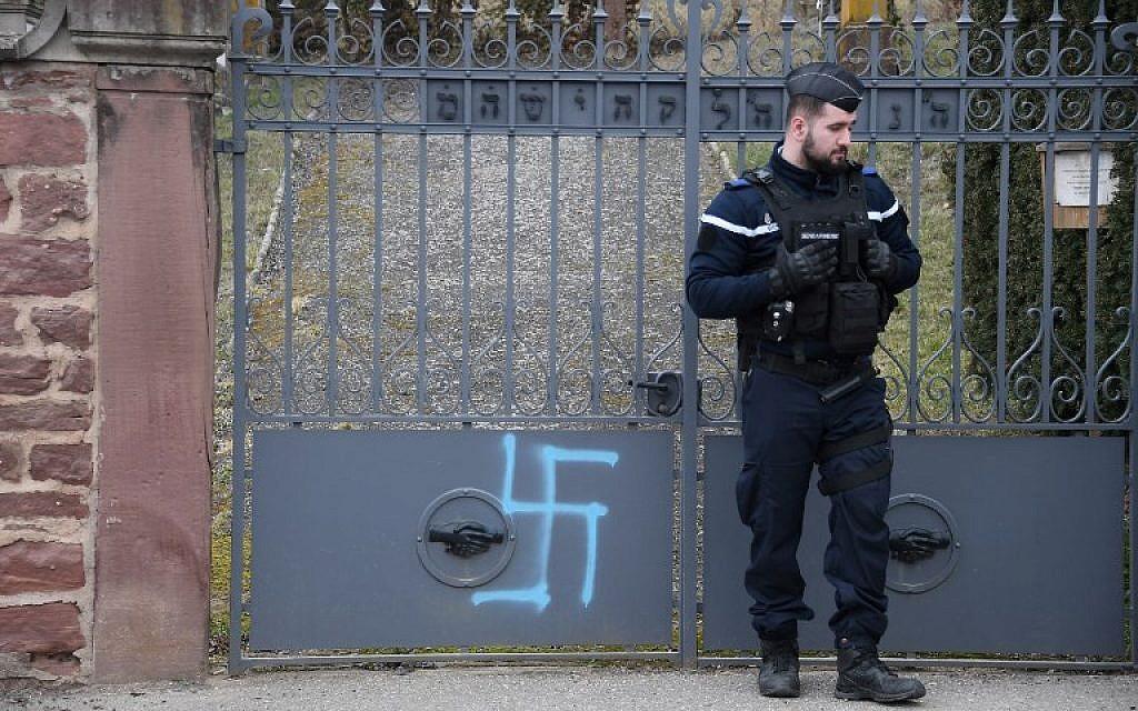 Une photo prise à Quatzenheim, France, le 19 février 2019 montre des croix gammées peintes sur le portail d'un cimetière juif, le jour d'une marche nationale contre la recrudescence des actes antisémites. - (Crédit : Frederick FLORIN / AFP)