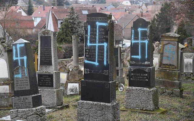 Une photo prise le 20 février 2019 à Quatzenheim montre des svastikas peintes sur des tombes dans un cimetière juif, le jour d'une marche nationale contre une recrudescence des attaques antisémites. - Environ 96 tombes ont été vandalisées dans un cimetière du village de Quatzenheim, près de la frontière avec l'Allemagne, dans la région Alsace. (Crédit : Frederick FLORIN / AFP)