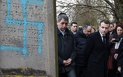 Le président français Emmanuel Macron observe une tombe vandalisée d'une croix gammée lors d'une visite au cimetière juif de Quatzenheim, le 19 février 2019, le jour des marches nationales contre la montée des attaques antisémites. (Photo par Frederick FLORIN / POOL / AFP)