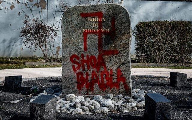 Une croix gammée et les mots 'Shoa blabla' inscrits sur le monument aux morts situé dans le jardin du Souvenir au cimetière de Champagne-au-Mont-d'Or, le 20 février 2019. (Crédit : JEFF PACHOUD / AFP)