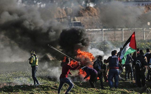Des émeutiers palestiniens brûlent des pneus lors d'une manifestation à proximité de la frontière le long de la frontière avec Israël, à l'est de la bande de Gaza, le 22 février 2019. (Crédit : MAHMUD HAMS / AFP)