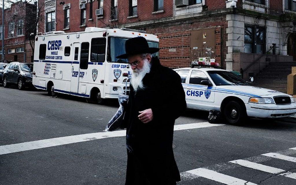 Des juifs orthodoxes dans le quartier de Crown Heights, à Brooklyn, le 27 février 2019. En arrière plan, un véhicule de la Crown Heights Shmira Patrol, une patroulle de sécurité mise en place par la communauté juive, dans un contexte d'antisémitisme ambiant. (Crédit : Angela Weiss / AFP)
