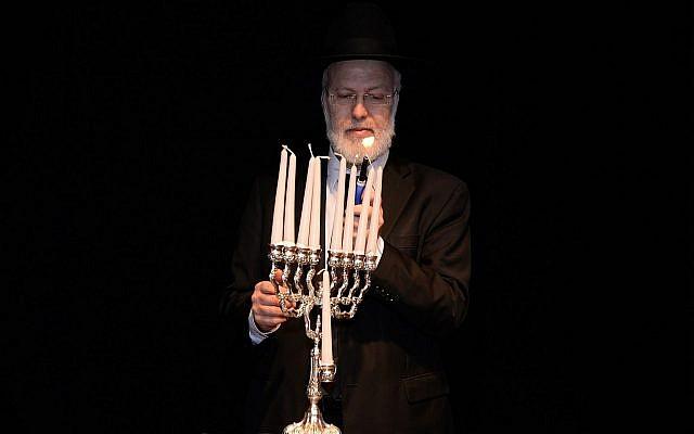 Sur cette photo du 5 décembre 2018, transmise par l'AMIA, le Grand Rabbin d'Argentine, Gabriel Davidovich, allume une hanoukia au centre communautaire juif AMIA à Buenos Aires. (Centre communautaire juif AMIA via AP)