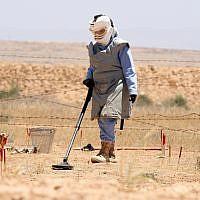 Un démineur jordanien examine un champ de mines à la frontière jordano-israélienne, le 28 juin 2011. (Crédit : AP/Nader Daoud)