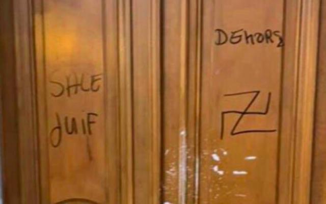 Tags antisémites sur une porte d'un immeuble du 14e arrondissement de Paris, le 21 février 2019 (Crédit : capture d'écran vidéo AFP)