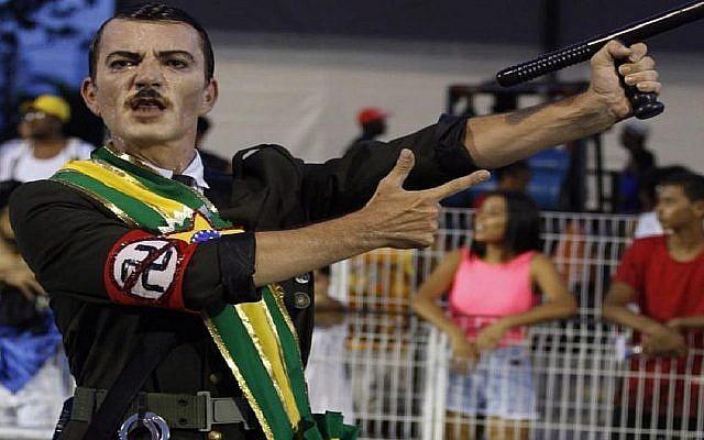 Un danseur d'une école de samba brésilienne lors de répétitions du Carnaval fait l'amalgame entre Adolf Hitler et Jair Bolsonaro, le nouveau président brésilien. (Crédit : Ismael Toledo via JTA)