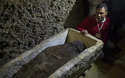 Photo d'illustration : Un archéologue observe une chambre funéraire récemment découverte dans la province désertique de Minya, au sud du Caire, en Egypte. le samedi 2 février 2019. (Crédit : AP/Roger Anis)