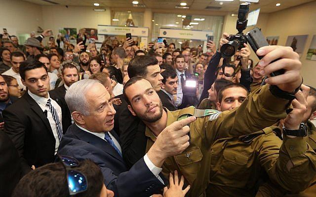 Le Premier ministre Benjamin Netanyahu prend un selfie avec un soldat durant un événement pour les soldats seuls à Tel Aviv, le 24 janvier 2019 (Crédit :  Marc Israel Sellem/Pool/Flash90)