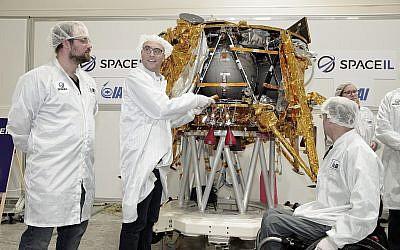 Yariv Bash, (à droite), Yonatan Winetraub, (au centre), et Kfir Damari, les fondateurs de SpaceIL, insérant une capsule témoin dans le vaisseau spatial Beresheet, le 17 décembre 2018. (Yoav Weiss)