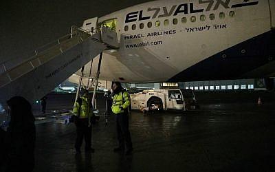 Des membres d'équipage se tiennent au pied de l'avion endommagé du Premier ministre Benjamin Netanyahu. (Crédit : Raphael Ahren/Times of Israel)