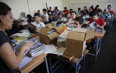 Des écoliers palestiniens reçoivent de nouveaux manuels dans leur classe lors de la rentrée de cette année dans l'une des écoles de l'UNRWA à Beyrouth au Liban, le 3 septembre 2018. (Hussein Malla/AP)