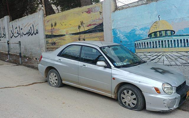 Une voiture avec les pneus crevés et des Etoiles de David peintes à la bombe spray dans le village cisjordanien de Ras Karkar, le 21 février 2019. (Photo personnelle)
