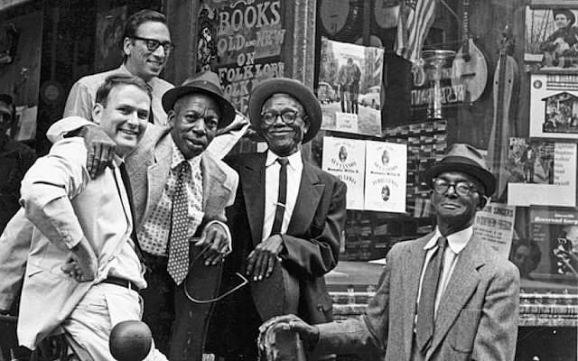 Izzy Young (au fond) au Folklore Center dans le quartier de Greenwich Village, New York, avec de gauche à droite : l'historien de la musique Sam Charters et les musiciens de blues Memphis Willie B., Furry Lewis, et Gus Cannon. (Crédit : Ann Charters via JTA)