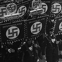 Des membres SS portent des drapeaux avec une croix gammées et des noms des régions et des villes allemandes alors qu'il marchent vers la mairie de Nuremberg, en Allemagne, le 10 septembre 1935, pour ouvrir la convention du Parti des Travailleurs d'Allemagne Nationale Socialiste (AP Photo).