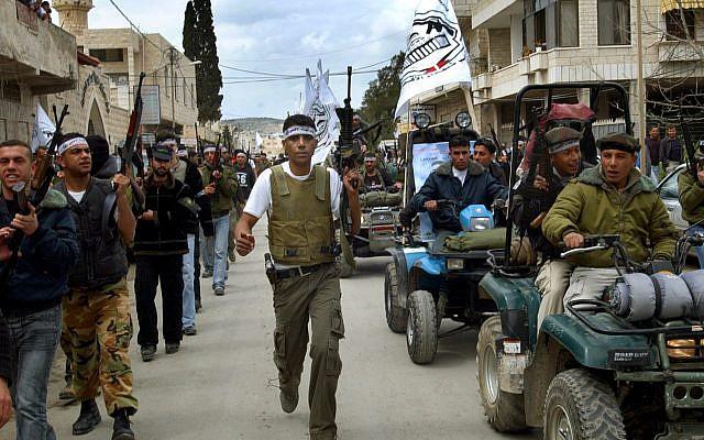 Zakaria Zubeidi, le commandant local de l'aile militaire du Fatah, les Brigades Al-Aqsa, et d'autres hommes armés manifestent dans les rues de la ville cisjordanienne de Jenin, le 2 avril 2005. (Mohammed Ballas/AP Photo)