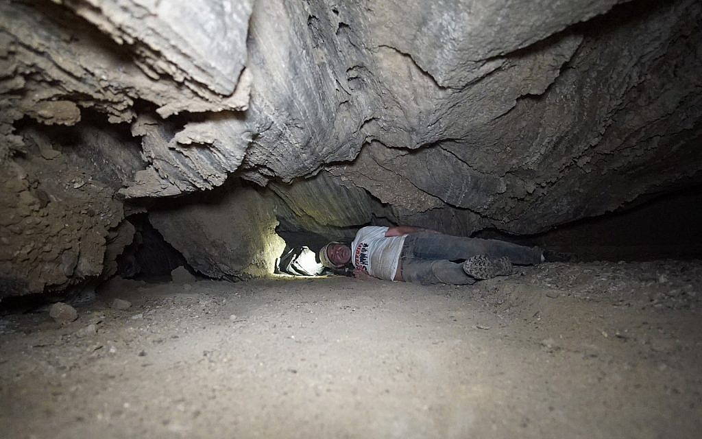 Des chercheurs se faufilent dans une brèche la grotte de Malham le 22 mars 2019. (Crédit : Anton Chikishev/Hebrew University)