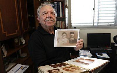 Samy Gryn, 78 ans,un des rares rescapés de la rafle du Vél d'Hiv en juillet 1942, montre une photo des proches, durant une interview à Tel Aviv, le 25 février 2019. (Crédit : MENAHEM KAHANA / AFP)