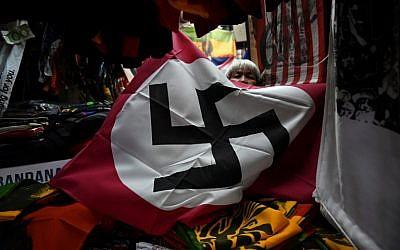 Un drapeau nazi en vente sur l'étal d'un marché de Bangkok, en Thaïlande., (Crédit : Lillian SUWANRUMPHA / AFP)