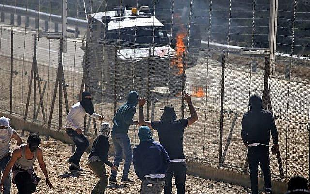 Un véhicule de l'armée israélienne en flammes durant des heurts avec des Palestiniens dans le village palestinien de Beit Sira, en Cisjordanie, le 8 mars 2019. (Crédit : Abbas Momani/AFP)